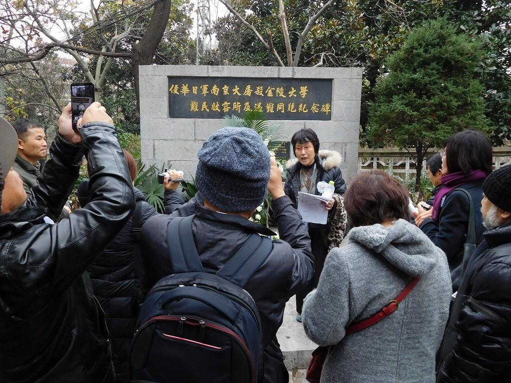 金陵大学難民収容所犠牲者記念碑の説明をする松岡環さん