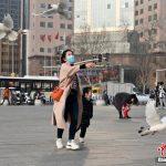 河北省石家荘市の広場で、鳩と遊ぶ親子